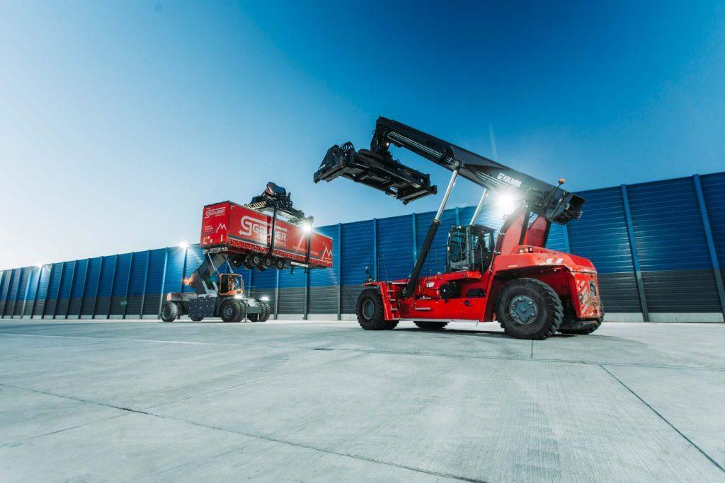 Containerterminal Südwestfalen. Stapler heben Trailer auf einen Wagon
