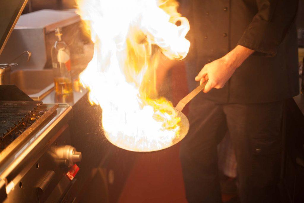 Koch schwenkt brennende Pfanne