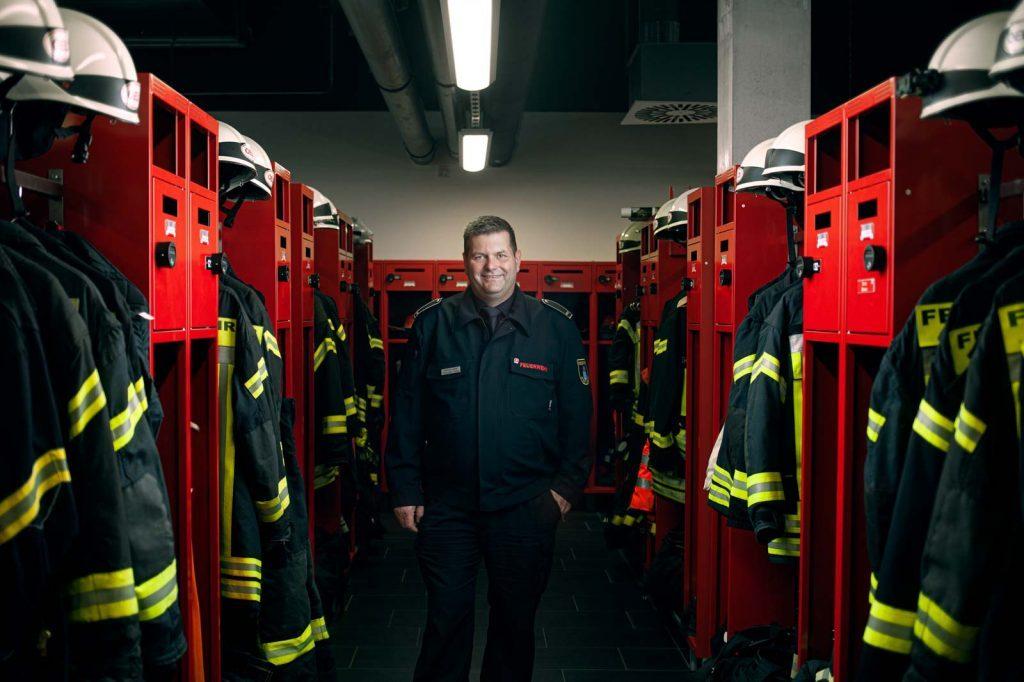 Leiter der Feuerwehr Minden in der Umkleide mit viel Ausrüstung
