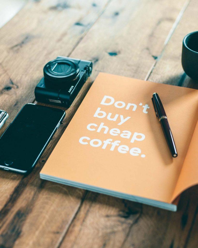 Zeitschrift liegt neben Kamera und Handy auf dem Tisch. Großer Aufdruck: Don't buy cheap coffe.