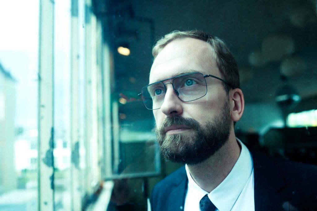 Mann mit Brille von Coblens schaut aus einem Industrie-Fenster