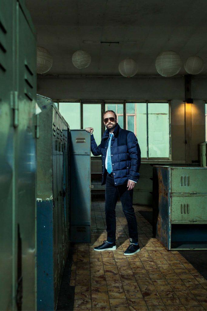 männliches Model mit Moncler Jacke und Sonennbrille in einem Industriebau